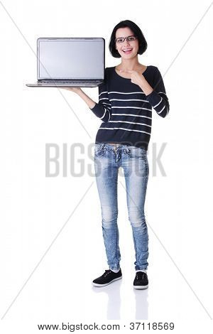 Full portrait of young woman holding and showing screen of 17 inch laptop