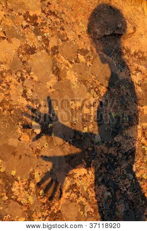 textured woman shadow on granite rock under warm sunset light
