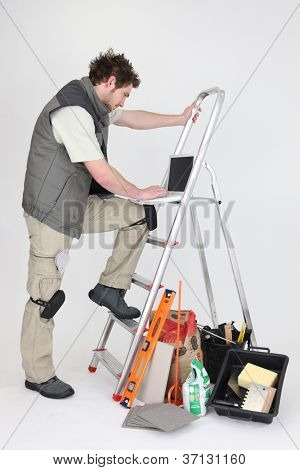 Tiler using computer leaning on a ladder