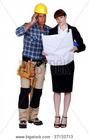 Unhappy and puzzled tradesman and engineer looking at a blueprint
