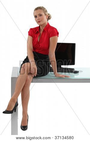 Blond businesswoman sat on desk