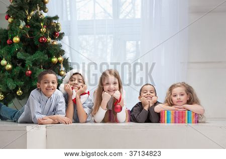 Smiling Children Holding Christmas Gifts