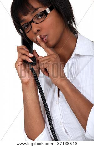 woman on the phone making a sign for silence