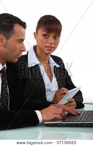 Woman taking notes as a businessman uses a computer