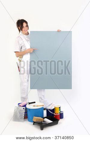 Decorador feminino, apontando para um cartaz em branco
