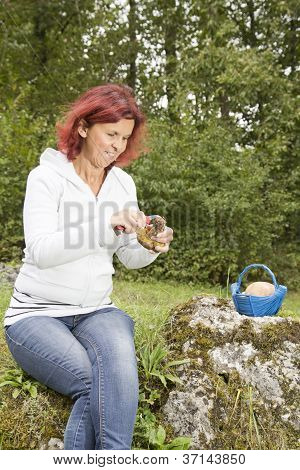 Cute woman cleaning mushroom Boletus Edulis