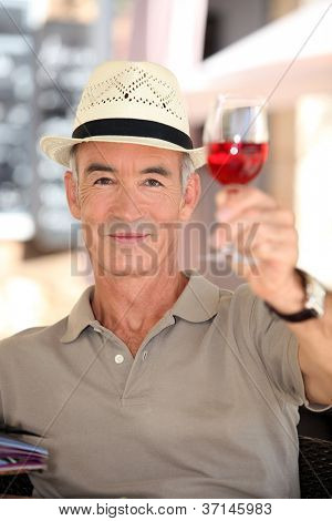 Elderly man toasting with glass of rose wine