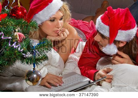 Young couple in Santa's hats with a laptop in white bed