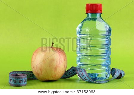 Bottle of water, apple and measuring tape on green background