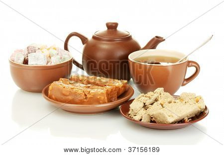 Teapot with cup and saucer with  oriental sweets - turkish delight, sherbet and halva  isolated on white