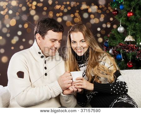 Portrait Of A Happy Young Couple Near The Christmas Tree