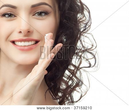 portrait of attractive  caucasian smiling woman brunette isolated on white studio shot head and shoulders face skin hand hair looking at camera applying cream