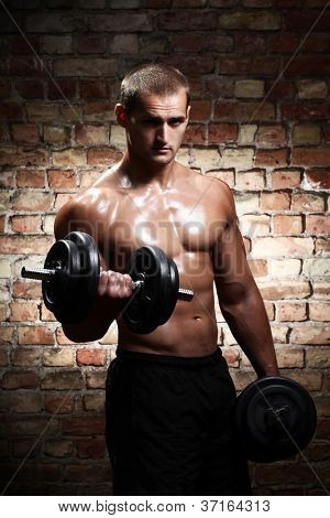 Young and muscular guy with dumbbells over brick wall