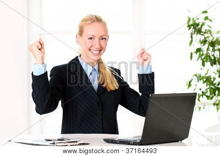 Excited young businesswoman in the office