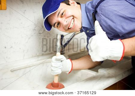 Portrait of a smiling plumber using a plunger