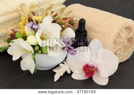 Freesia, orchid, honeysuckle and lavender flower blossom, aromatherapy spa bottle, towels and ex foliating scrub with coral shell over slate background.