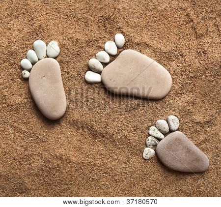 trace feet steps made of a pebble stone walking on the sea sand ,  pattern texture backdrop