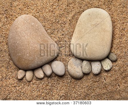 trace feet made of a pebble stone on the sea sand texture backdrop