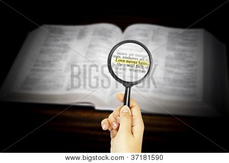 marked phrase in Holy Bible under magnifying glass