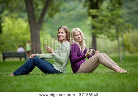 Side view portrait of happy young female friends with cellphones sitting back to back in park