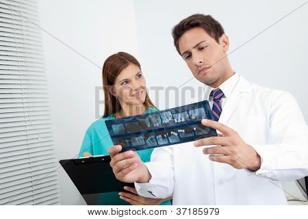 Dentist with dental nurse analyzing patient's X-ray report in clinic