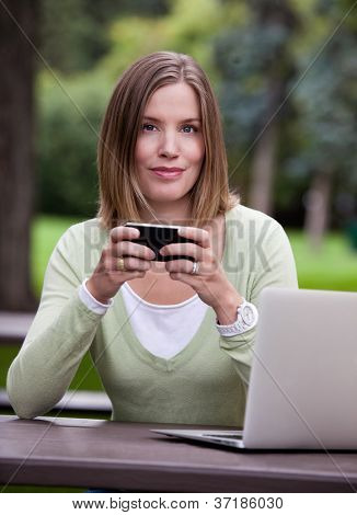 Portrait of attractive woman in park with mobile phone and computer