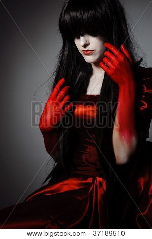 Young mysterious fashion witch vampire with black hairs against the dark background