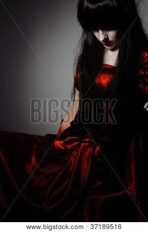 Vampiro de bruja misteriosa joven con pelos negros sobre fondo oscuro