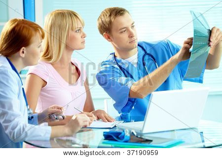 Portrait of young doctor commenting x-ray exam results to his colleague and patient