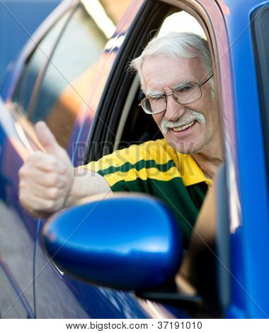 Happy senior man with thumbs up driving a car