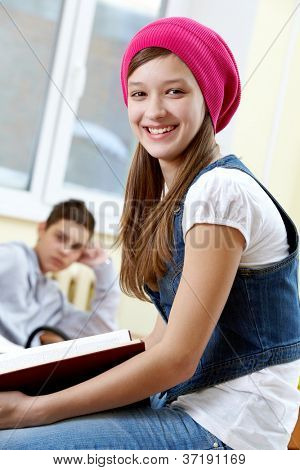 Portrait of smart girl looking at camera with her classmate on background