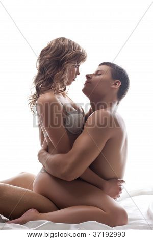 Couple playful lovers sit in bed - sexual games