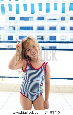 Blond kid girl with summer swimsuit with hands victory sign smiling