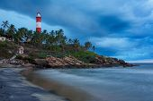 Gathering storm on beach and Kovalam (Vizhinjam) lighthouse on stormy sunset. Kerala, India
