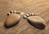 picture of splayed  - two trace feet made of a pebble stone on the sea sand desert  - JPG