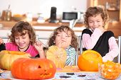 Giggling girls carving pumpkins