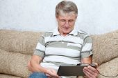 Senior Adult Caucasian Man Interested With A New Tablet Computer, Sitting On Sofa In Domestic Room poster