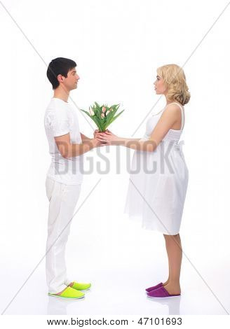 Young attractive couple: pregnant mother and happy father with the flower bouquet isolated on white