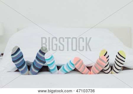Family's feet in stripey socks at home in bed