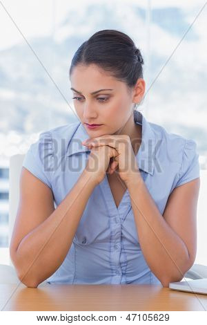Sad businesswoman sitting at her desk in her office
