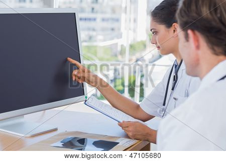 Doctor pointing at the screen of a computer while working with a colleague