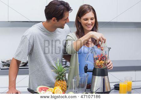 Paar setzen verschiedene Früchte in einen Mixer