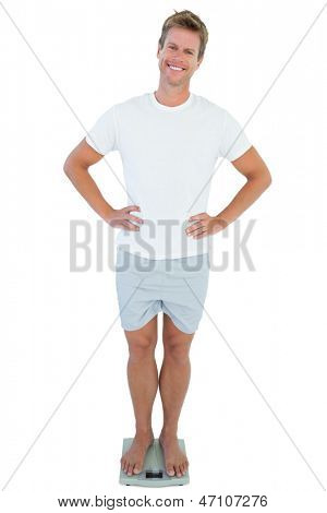 Cheerful man standing on a weighing scale on white background