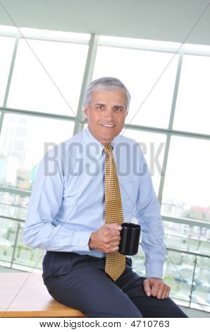 Middle Aged Businessman Sitting On Desk With Coffee