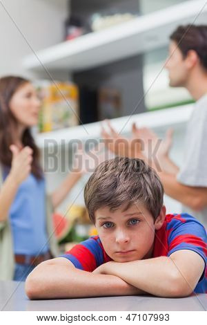 Sad little boy listening to his parents arguing in the kitchen