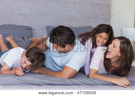 Parents tickling their children on bed at home