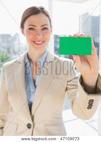 Smiling businesswoman holding up green business card in bright office