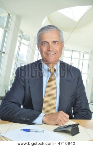 Middle Aged Businessman Seated At His Desk