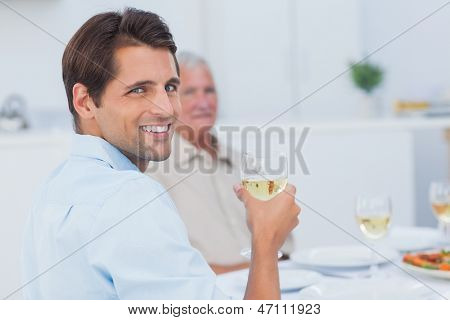 Attractive man holding a glass of white wine and looking at camera