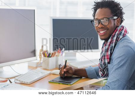 Smiling graphic designer using a graphics tablet in a modern office